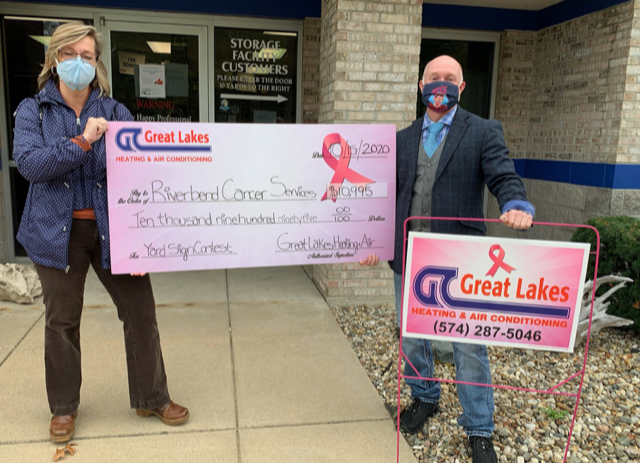 A check to Riverbend Cancer Services from Great Lakes Heating & Air Conditioning raised during the yard sign contest